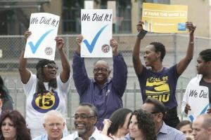 People hold up signs at a celebration event for the signing of an ordinance raising the city's minimum wage.