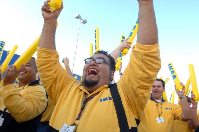 In this photo provided by IKEA, employee Adrian Gonzalez, center, of Burbank, Calif., helps pump up the crowd waiting to enter the new IKEA store during grand-opening ceremonies in Orlando, FL (AP Photo/Phelan M. Ebenhack, IKEA)
