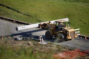Construction workers continue to unload pipe from a flatbed trailer truck after one of the pipe pieces rolled over and killed a 28-year-old construction worker southwest of the Petaluma Boulevard South exit of Highway 101 in Petaluma, on Wednesday, April 15, 2015. (BETH SCHLANKER/ PD)