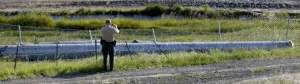 A member of the Sonoma County Sheriff's Office takes a photo of the pipe that rolled over and killed a 28-year-old construction worker in Petaluma on Wednesday, April 15, 2015. (BETH SCHLANKER/ PD)